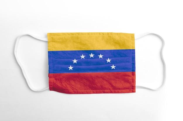 Gezichtsmasker met gedrukte vlag van venezuela, op witte achtergrond, geïsoleerd.