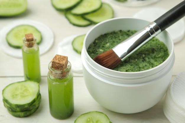 Gezichtsmasker met komkommer. cosmetica met komkommerextract op een witte houten tafel. spa. schoonheid.