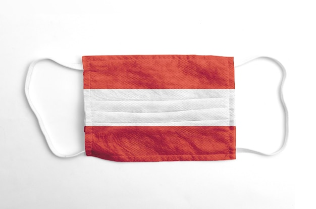 Gezichtsmasker met opgedrukte oostenrijkse vlag, op wit.