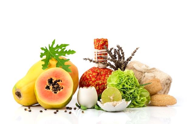 Gezichtsmasker met papaja fruit, wit ei, haver en citroen geïsoleerd op een witte achtergrond.
