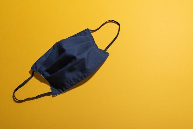 Gezichtsmasker omgekeerd achtergezicht op geel bureau