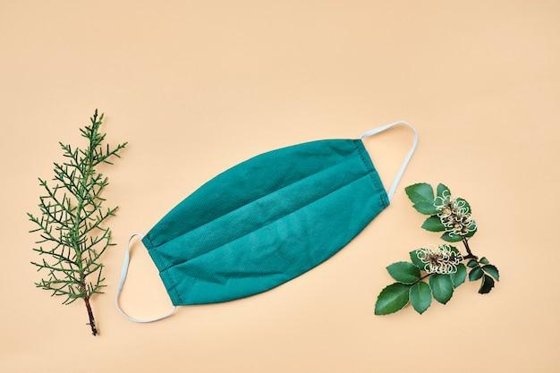 Gezichtsmasker op een pastelgele muur vergezeld van dennenbladeren en lenga. bovenaanzicht, kopieer ruimte.
