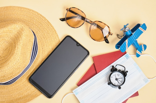Gezichtsmasker, strohoed, smartphone, zonnebril, wekker en paspoort op beige achtergrond, reizen tijdens lockdown, veilig strandvakantieconcept