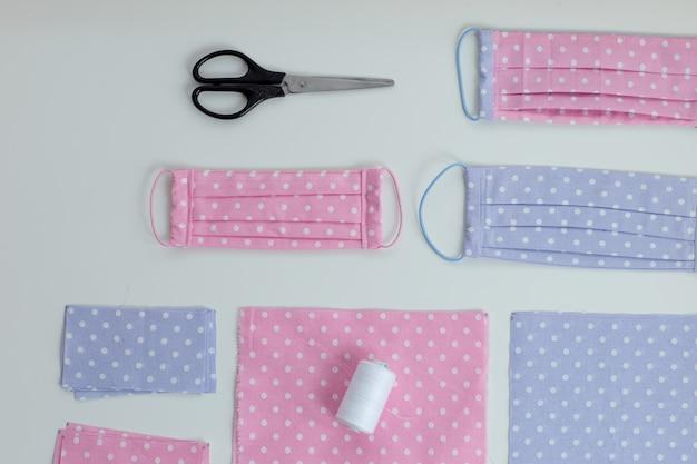 Gezichtsmasker tegen met de hand gemaakt virus, naai beschermend masker, stukken gestippelde doek, draden op witte tafel. plat lag met roze en blauwe doek, schaar en draden.