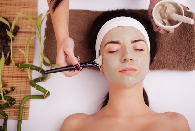 Gezichtsmasker toepassen op vrouwengezicht bij schoonheidssalon