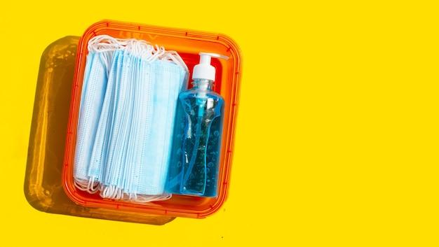 Gezichtsmaskers met alcohol vloeibaar gel-ontsmettingsmiddel op geel oppervlak