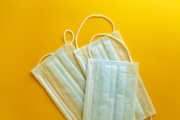 Gezichtsmaskers op gele achtergrond, bovenaanzicht. medische sanitaire chirurgische maskers, ademende anti-stof ademende 3-laags oorlus mond gezichtsmaskers bieden bescherming tegen de verspreiding van infectie