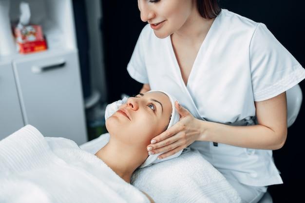 Gezichtsmassage aan vrouwelijke patiënt, cosmetologie kliniek