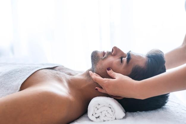 Gezichtsmassage. close-up van een jonge man krijgt spa-behandeling.