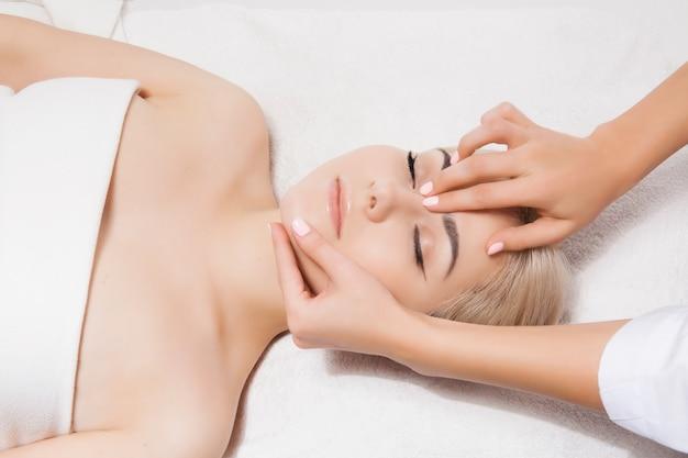 Gezichtsmassage. close-up van een jonge vrouw die kuuroordmassage in een schoonheid en kuuroordsalon ontvangt door schoonheidsspecialist. spa huid- en lichaamsverzorging. schoonheid gezichtsverzorging. cosmetologie.