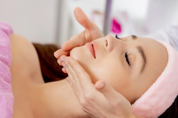 Gezichtsmassage. close-up van jonge vrouw die spa-massagebehandeling krijgt bij beauty spa salon. spa huid- en lichaamsverzorging. facial beauty treatment.cosmetologie.
