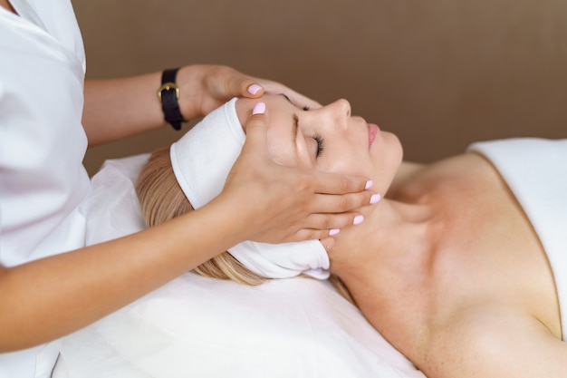 Gezichtsmassage. close-up van volwassen vrouw die spa-massagebehandeling krijgt bij beauty spa salon. spa huid- en lichaamsverzorging. gezichts schoonheidsbehandeling. cosmetologie.