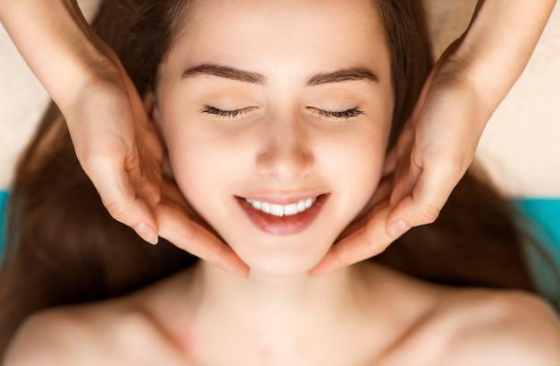 Gezichtsmassage en verjongende oefeningen voor het gezicht van de vrouw in de beauty spa