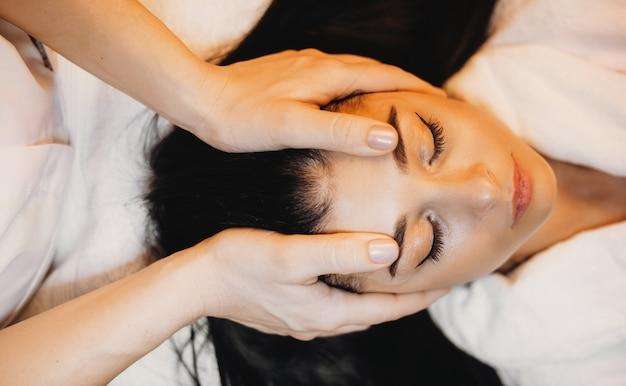 Gezichtsmassage gedaan door een professionele masseur in de kuuroordsalon voor een donkerbruine vrouw