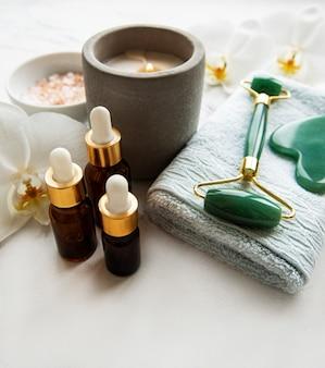 Gezichtsmassage jade roller met cosmetisch product op witte marmeren achtergrond