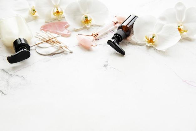 Gezichtsmassage jade roller met cosmetisch product op witte marmeren tafel