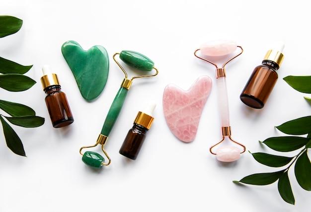 Gezichtsmassage met jade roller en cosmetisch product op een witte ondergrond