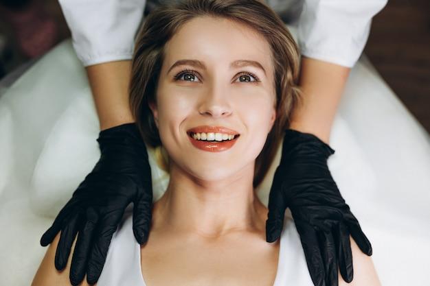 Gezichtsmassage schoonheidsbehandeling. close-up van het gezicht van een jonge vrouw die op de rug ligt en gezichtsmassage krijgt, knijp- en roltechniek.