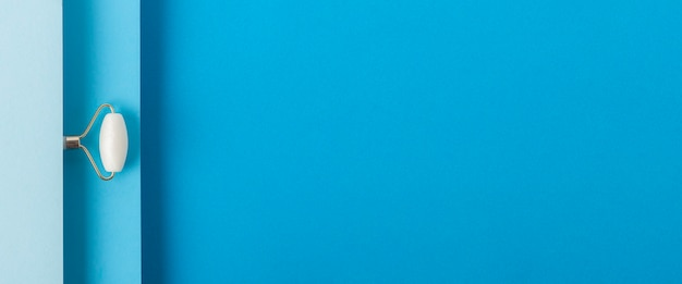 Gezichtsmassager op gevouwen blauwe kartonnen achtergrond. bovenaanzicht, plat gelegd. banier.