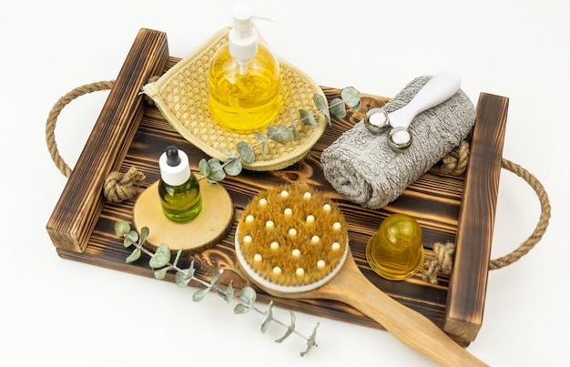 Gezichtsolie en gezichtsroller, borstel voor droge massage en een katoenen handdoek liggen op een houten blad