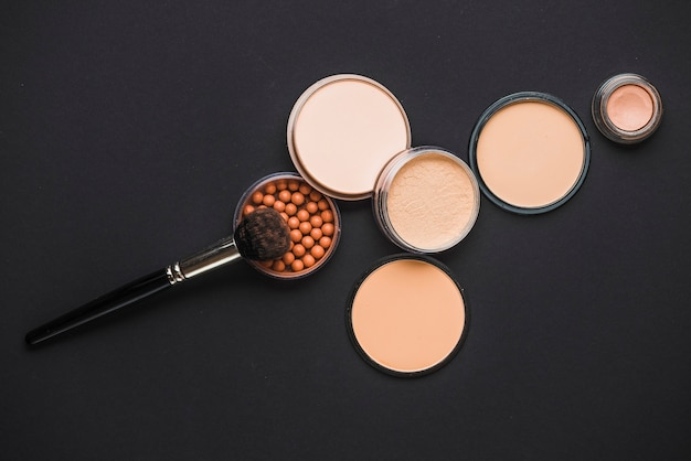Gezichtspoeder; bronzing parels en make-up borstel op zwart oppervlak