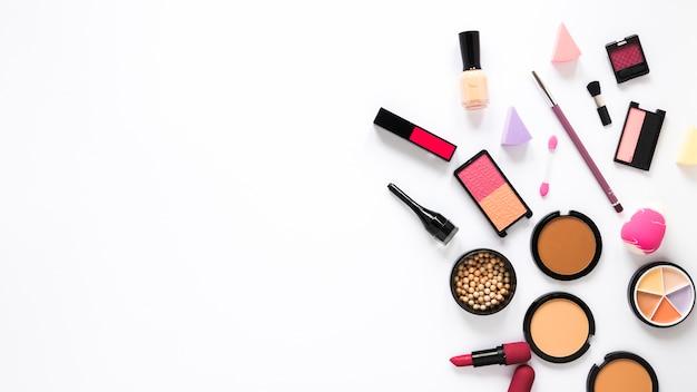 Gezichtspoeders met oogschaduw en lippenstift op tafel