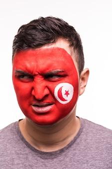 Gezichtsportret van gelukkige ventilatorsteun tunesisch nationaal team met geschilderd gezicht dat op witte achtergrond wordt geïsoleerd