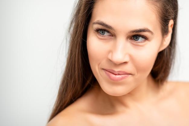 Gezichtsportret van jonge kaukasische vrouw met naakte schouders en natuurlijke make-up op witte muur