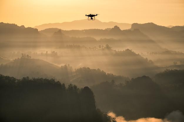 Gezichtspunt gouden zonneschijn mist berg met drone vliegtuigen vliegend onderzoek