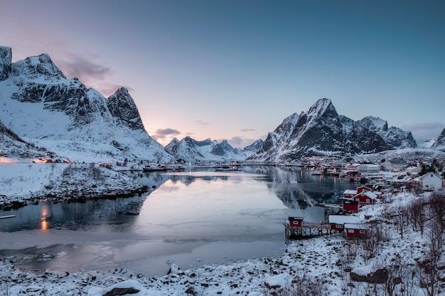 Gezichtspunt van vissersdorp met haven in sneeuwvallei en ijsoverzees bij ochtend