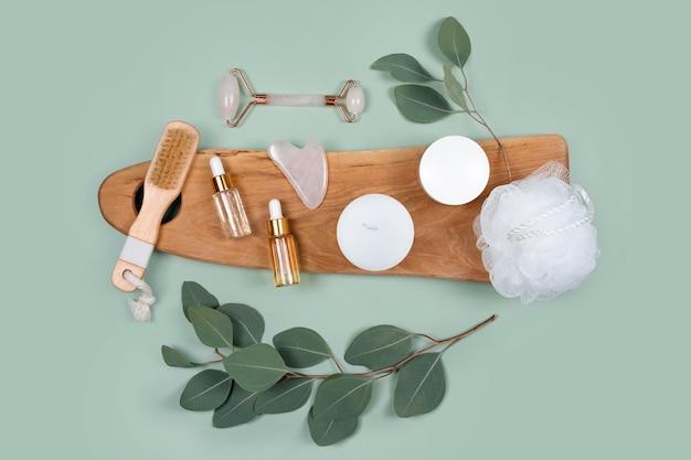 Gezichtsroller, etherische oliën, cosmetische serums, gezichtscrème op groene achtergrond met natuurlijke eucalyptusbladeren