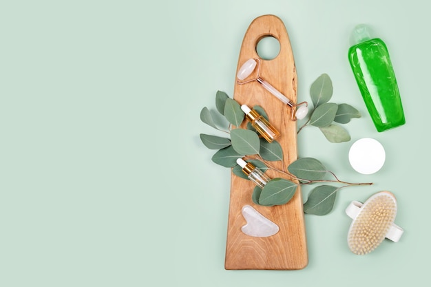 Gezichtsroller, etherische oliën, cosmetische serums, massageborstel en bodylotion met natuurlijke eucalyptusblaadjes