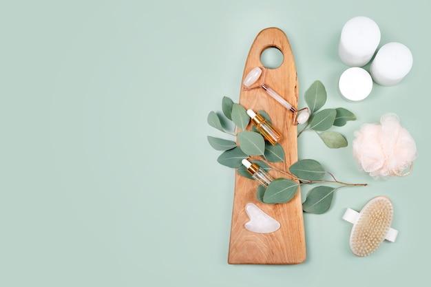 Gezichtsroller, etherische oliën, cosmetische serums, massageborstel en kaarsen met natuurlijke eucalyptusbladeren