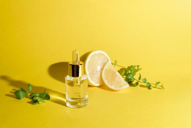 Gezichtsserum met citrusvruchten, citroen en vitamine c in een glazen flesje met een pipet op een gele achtergrond