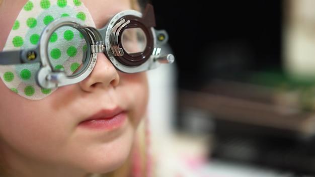 Gezichtsvermogen controleren. kaukasisch meisje met visuele handicaps. medische behandeling en revalidatie