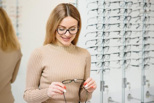Gezichtsvermogen en visie concept - jonge zakenvrouw bril kiezen bij optica winkel