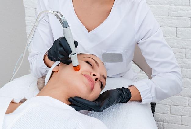 Gezichtsverzorging. close-up van vrouwengezicht reiniging bij cosmetology-kliniek, het stofzuigen