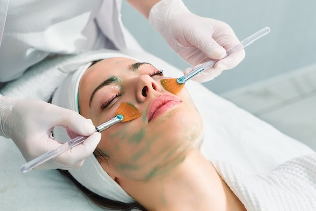Gezichtsverzorging. een masker wordt aangebracht op het gezicht van een vrouw in een cosmetische kliniek. detailopname
