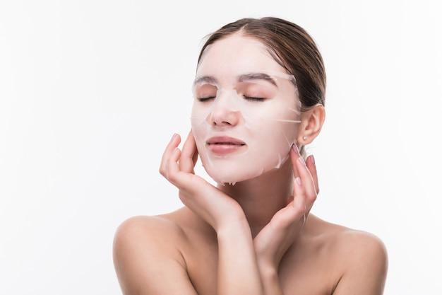 Gezichtsverzorging en schoonheidsbehandelingen. jonge vrouw met een doek bevochtigend masker op haar gezicht dat op grijze muur wordt geïsoleerd