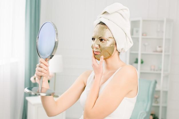 Gezichtsverzorging en schoonheidsbehandelingen. vrouw met een blad hydraterende gouden masker op haar gezicht en witte handdoek op het hoofd, kijkend naar de spiegel.