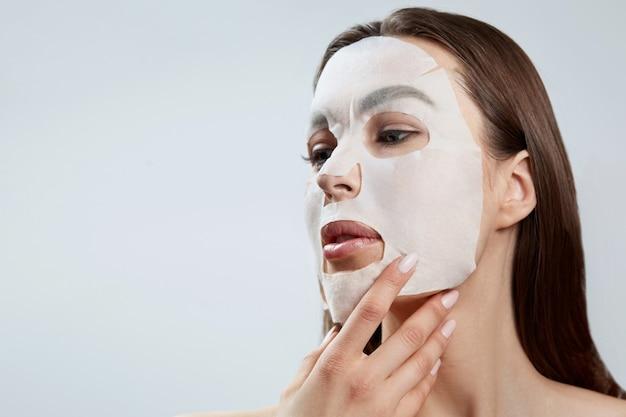 Gezichtsverzorging en schoonheidsbehandelingen. vrouw met een vochtinbrengend masker van de doek. cosmetische procedure. spa en cosmetologie