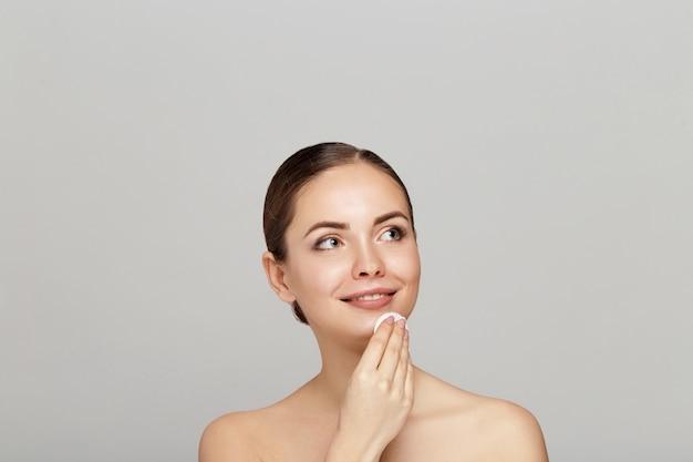Gezichtsverzorging. mooie vrouw make-up met wattenschijfje verwijderen