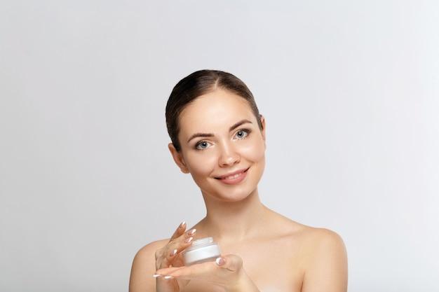 Gezichtsverzorging. mooie vrouw met gezonde gladde gezichts schone huid fles cosmetische crème te houden. model met schoonheidsgezicht. moisturizer gezichtsbehandeling. cosmetology.spa.