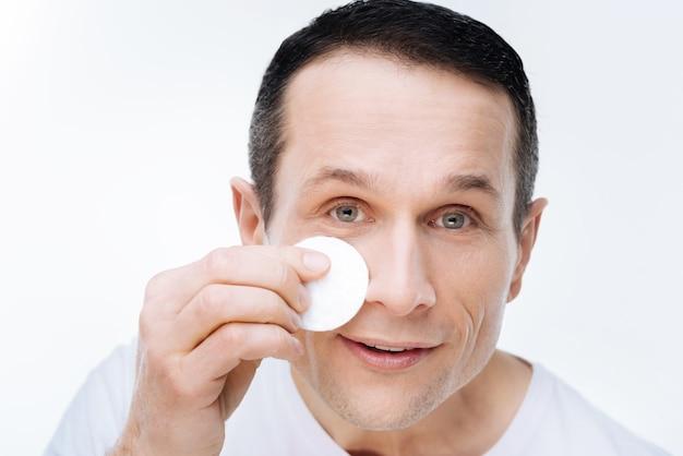 Gezichtsverzorging. portret van een aardige knappe positieve man die een wattenschijfje vasthoudt en glimlacht tijdens het schoonmaken van zijn gezicht met een wattenschijfje