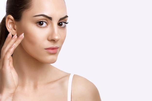 Gezichtsverzorging. portret van mooie jonge vrouw wat betreft gezicht. natuurlijke make-up