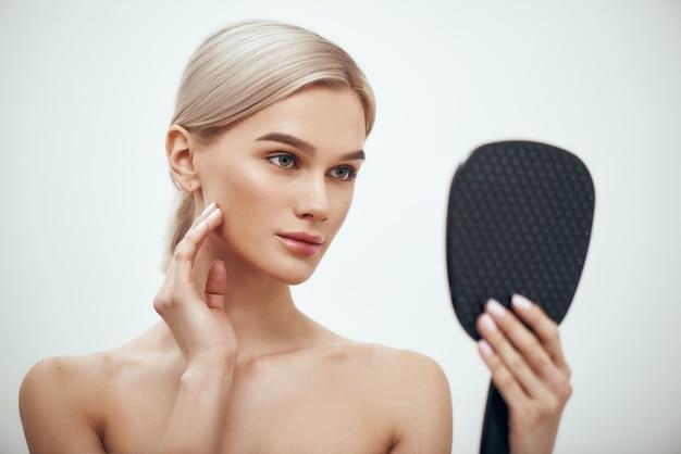 Gezichtsverzorging portret van prachtige blonde vrouw die haar gezicht aanraakt en in een kleine spiegel kijkt