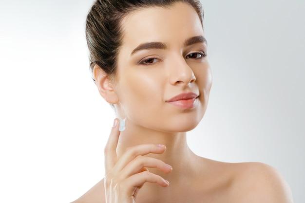 Gezichtsverzorging. vrouw crème toe te passen en glimlachen. portret van jonge vrouw met cosmetische crème op huid.