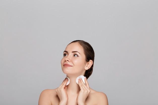 Gezichtsverzorging. vrouw die gezichtsreiniger op gezicht close-up toepast. meisje dat cosmetisch product op de huid reinigt