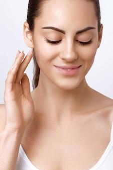 Gezichtsverzorging. vrouwelijke toepassing van crème en smiling.portrait van jonge vrouw met cosmetische crème op de huid. close-up van mooi meisje met schoonheidsproduct op zachte huid, natuurlijke make-up gezicht aan te raken.