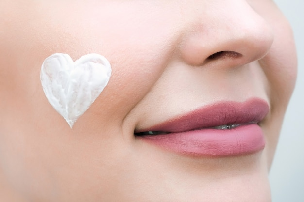 Gezichtsverzorgingsconcept. een jonge vrouw heeft een hart van crème op haar gezicht.